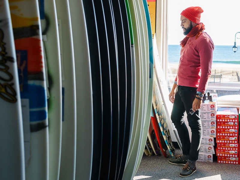 Image of surfer watching at surfboards in surf shop