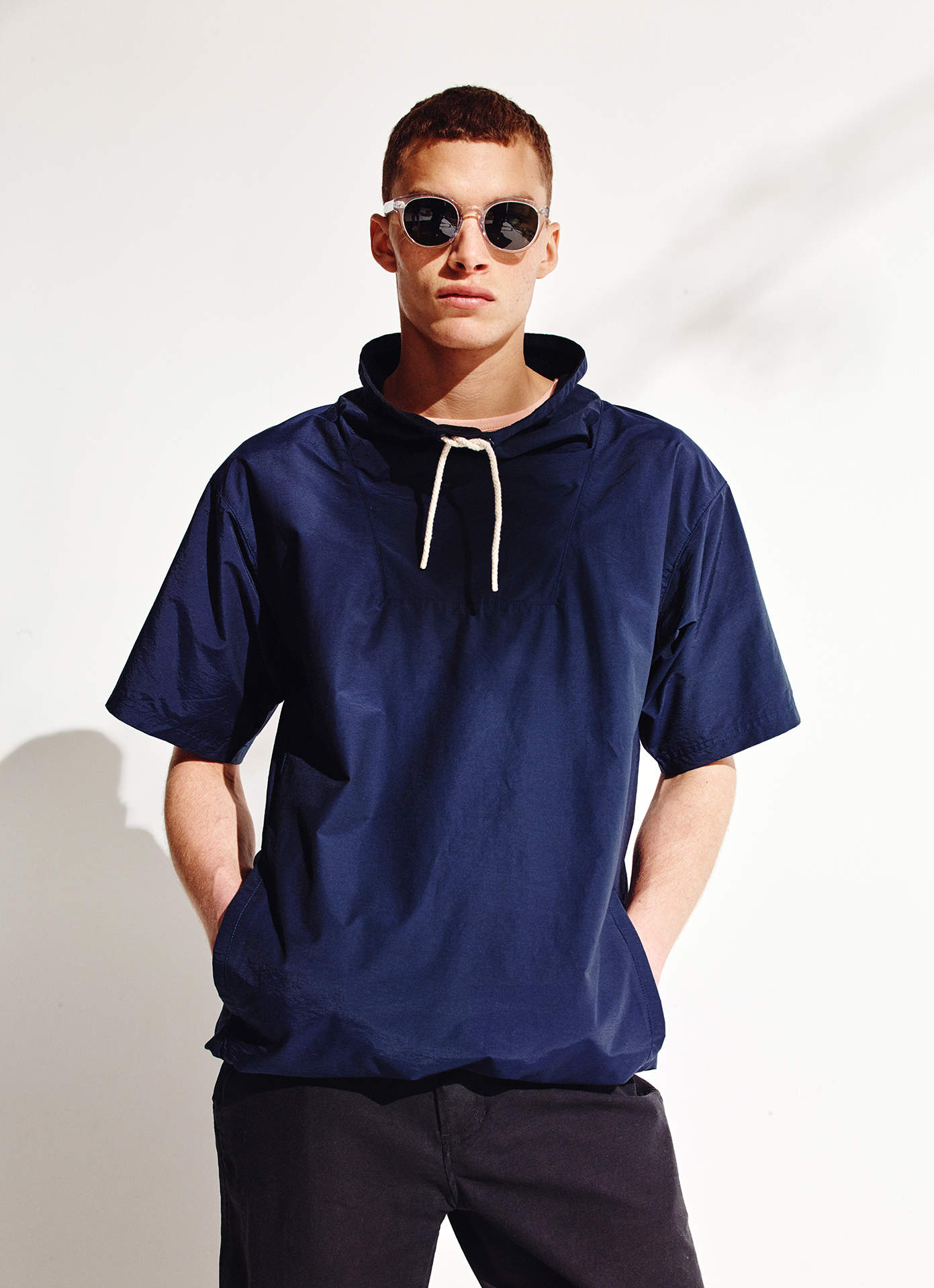 A photo of a model wearing saturdays nyc caleb windbreaker and sunglasses