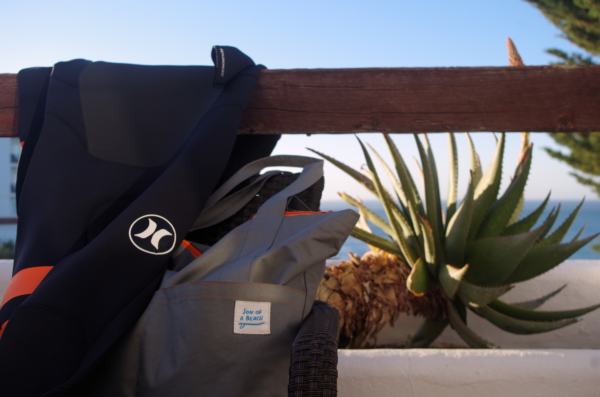 Hurley wetsuit and Son of a Beach tote bag on a balcony near a beach