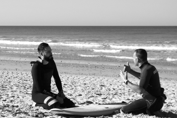 Surfing instructor and student on the beach in Conil, Spain