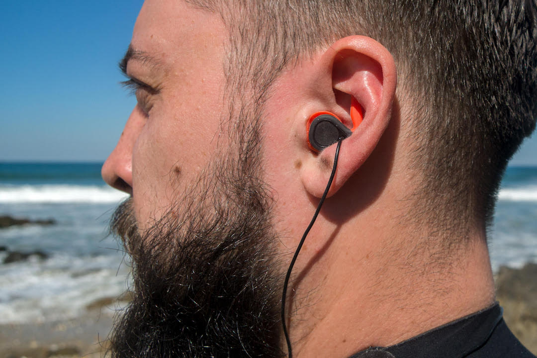Picture showing a surfer with an earplug into the ear
