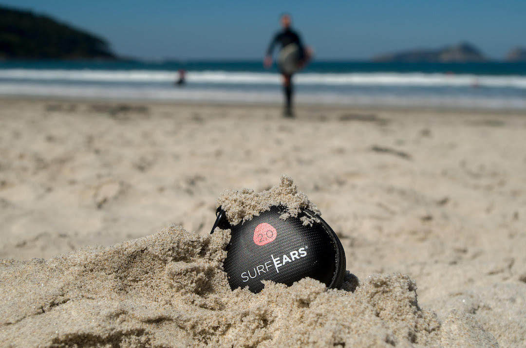 SurfEars storage case lying on the beach in the sand