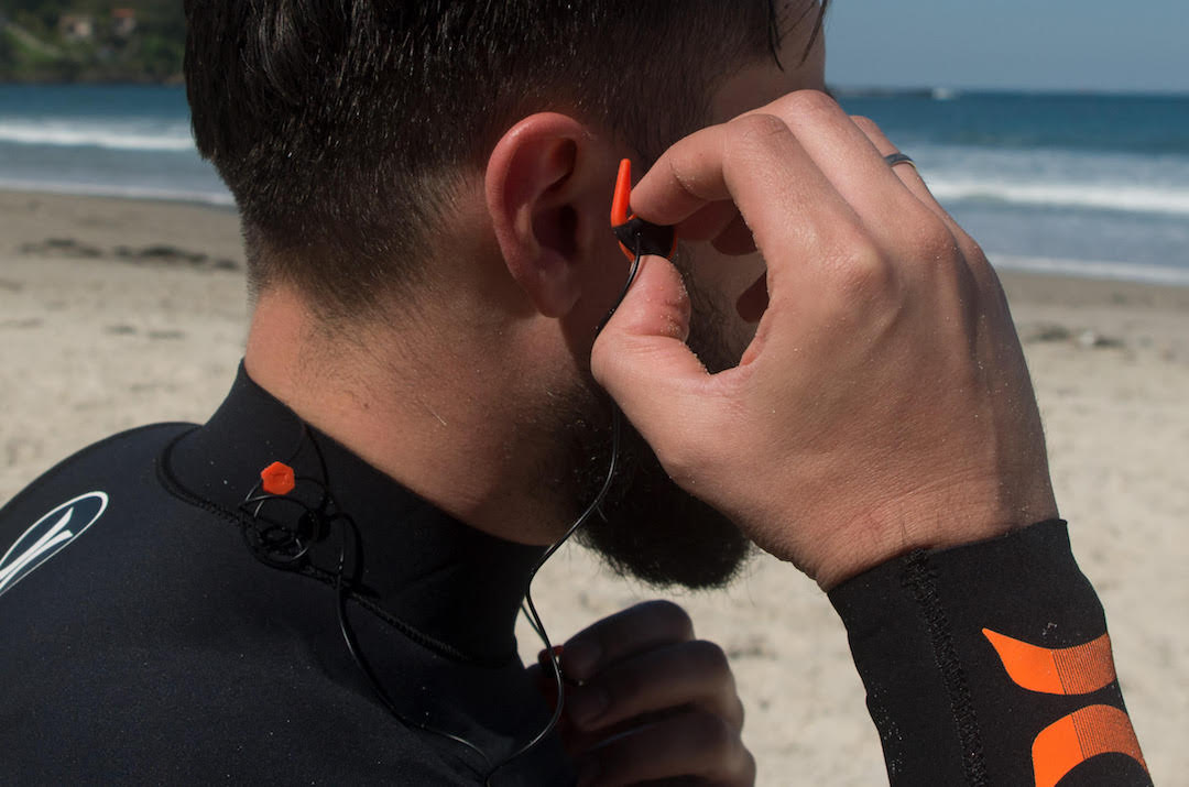 Picture showing a surfer putting earplug into the ear