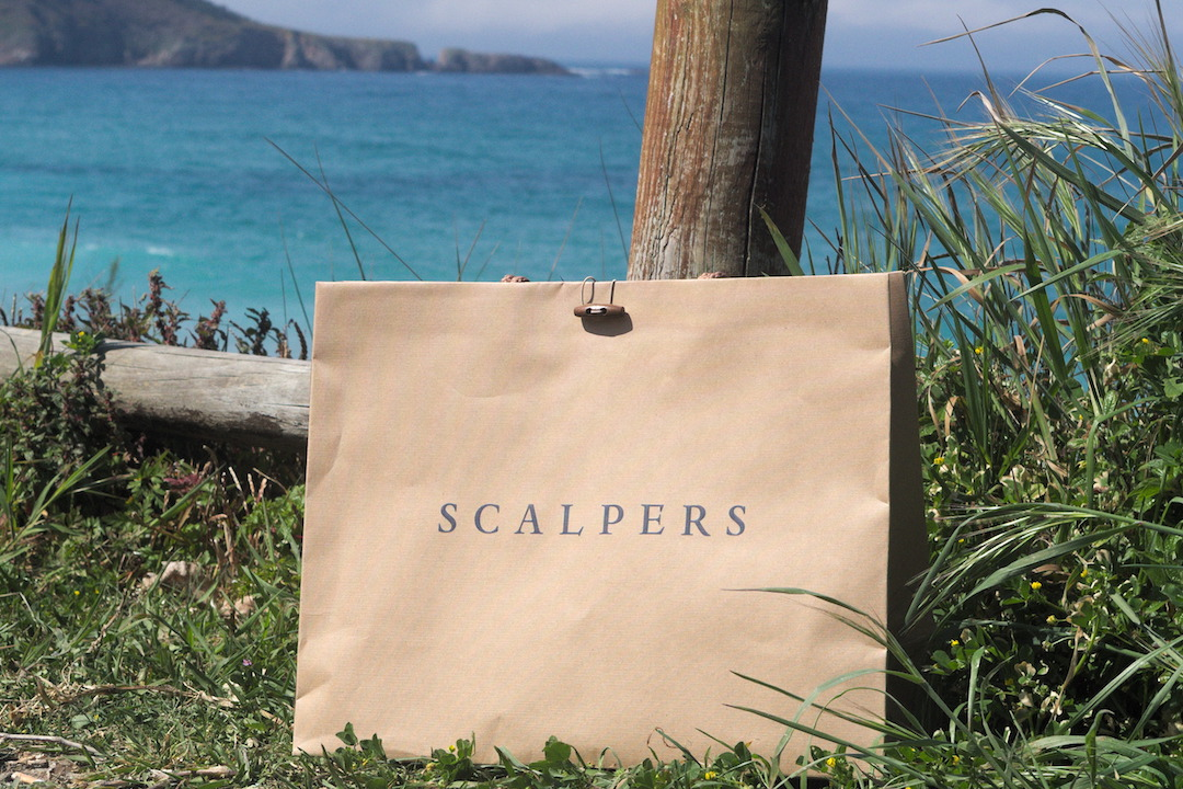 A picture of a Scalpers shopping bag on a beach