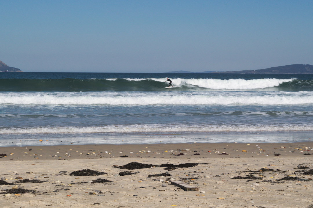 Picture of a surfer riding a wave on Patos beach in Galicia