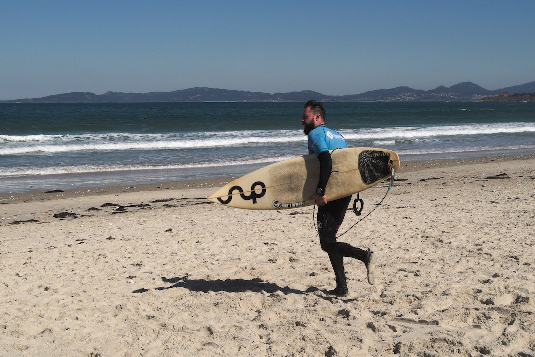 Zdjęcie surfera biegnącego do wody na plaży w Patos