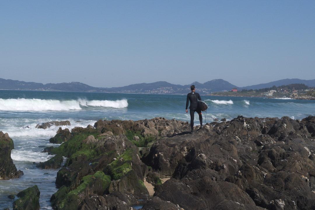 Zdjęcie surfera stojącego na skałach na plaży w Patos