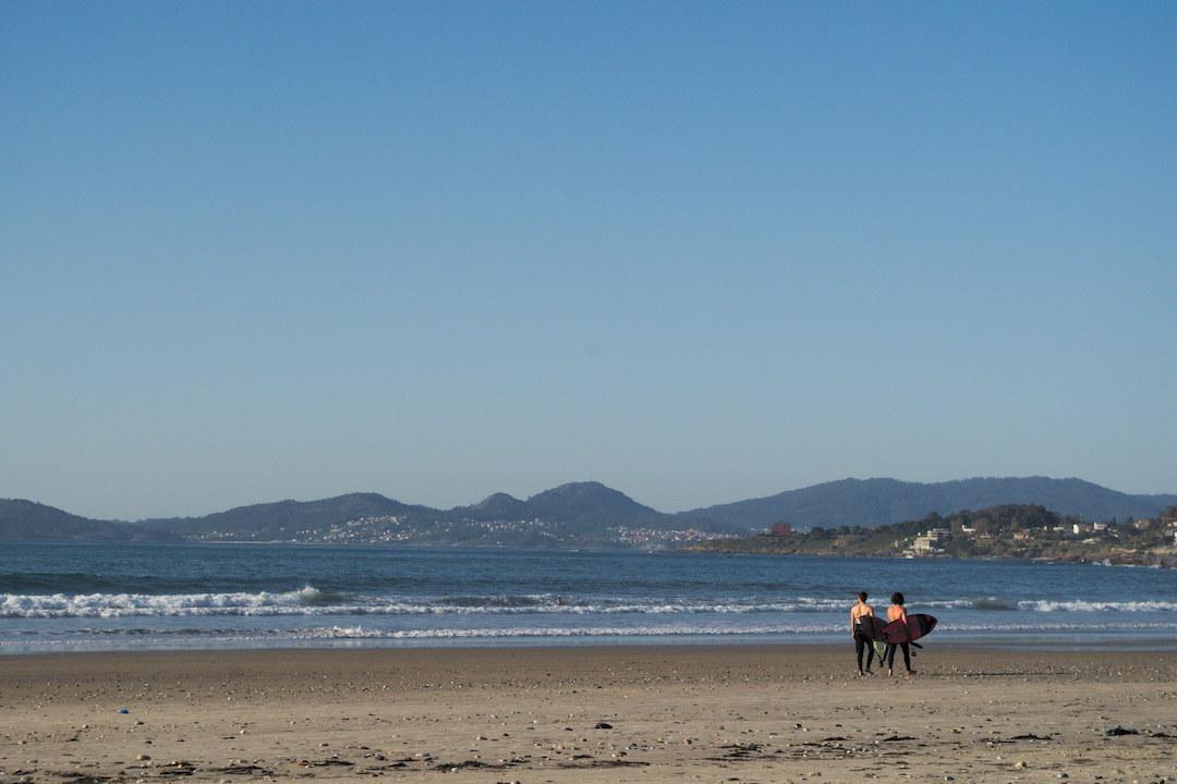 Zdjęcie dwóch surferów idących po plaży w Patos