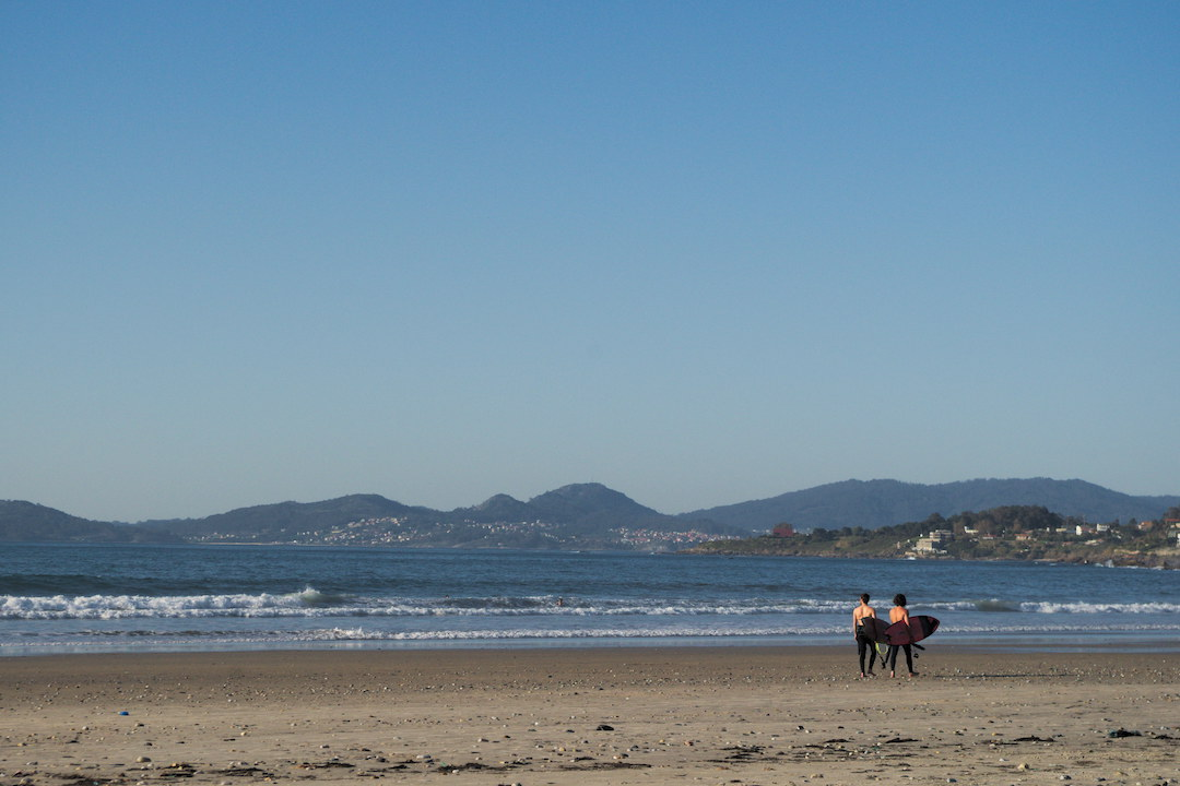 Picture of two surfers walking on Patos beach in Galicia