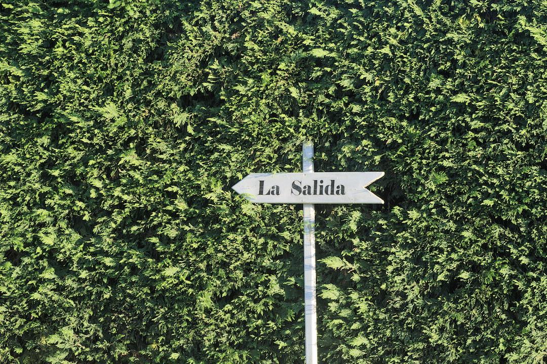 Zdjęcie tabliczki z napisem La Salida na tle wysokiego, zielonego żywopłotu