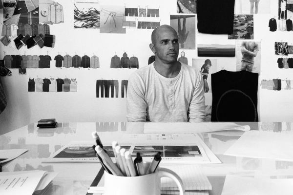 Picture of Kelly Slater sitting in front of the table with clothing pictures around him