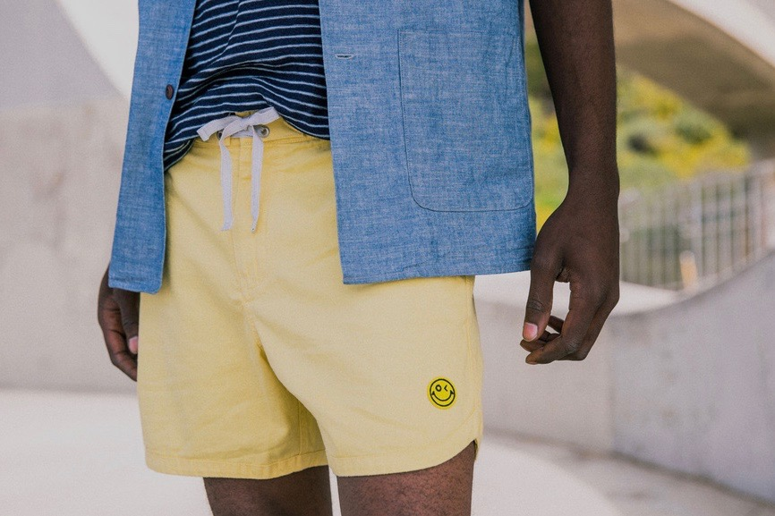 Picture of model presenting Outerknown Mr Porter collection of yellow shorts and denim shirt