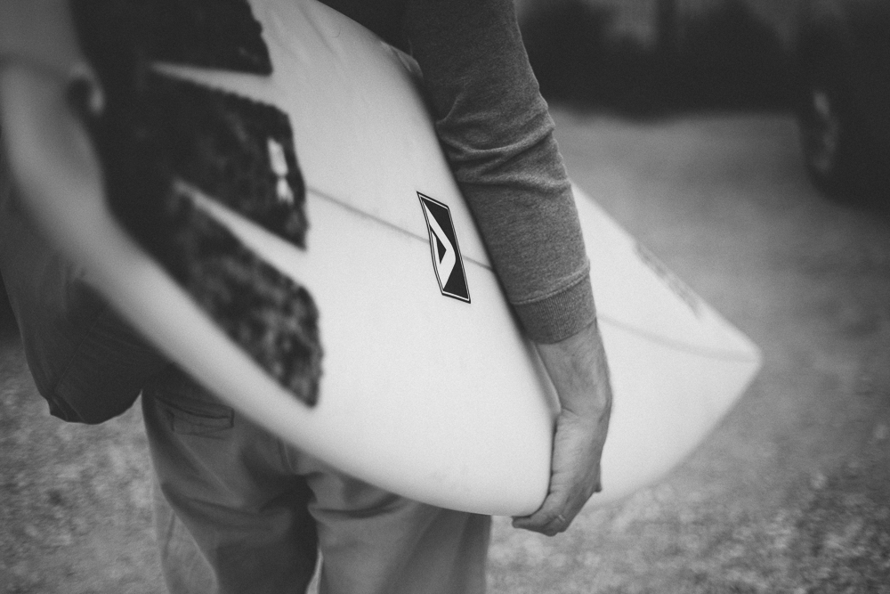 Picture showing a surfer carrying a surfboard under his arm