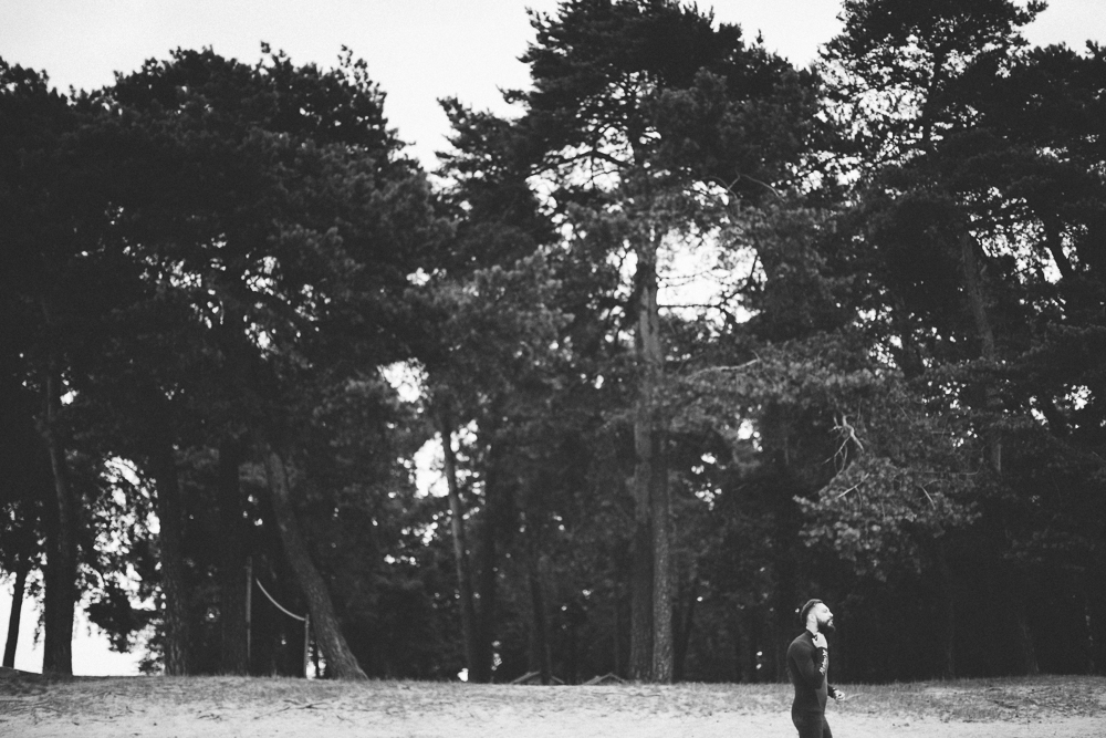 Picture of a surfer standing in front of big trees on the beach