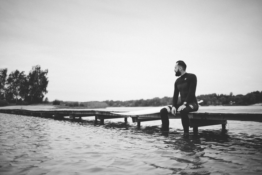 Picture of a surfer who sits on a lake bridge