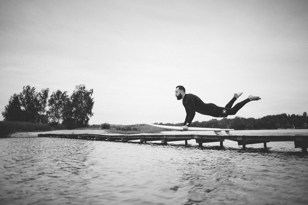 Picture of a surfer jumping of a lake bridge