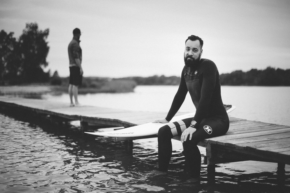 Picture of a surfer who sits on a lake bridge looking towards camera