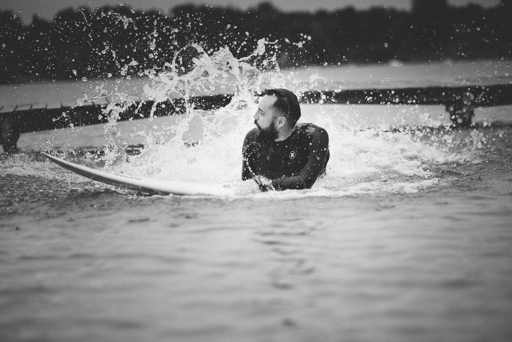 Picture of a surfer in water with big splash behind him
