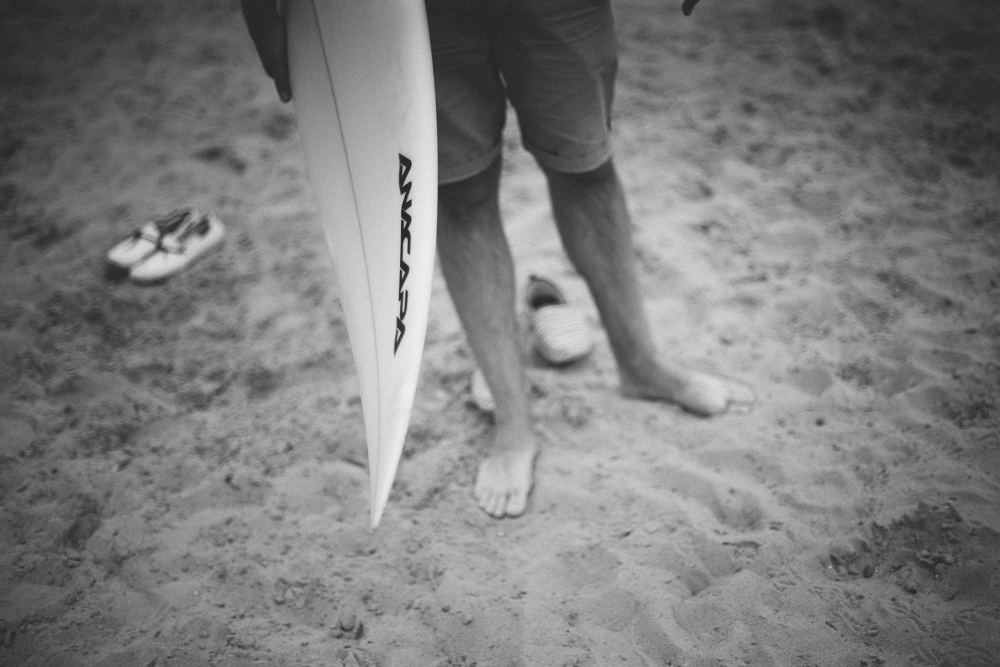 Picture showing legs of a surfer standing on sand with board in his hand