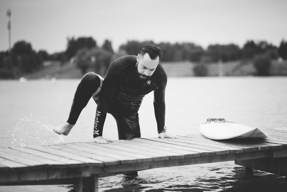 Picture of a surfer who is getting out of the water on a lake bridge