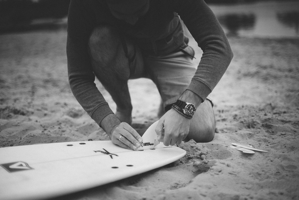 Picture showing a surfer who is installing fins in his boards