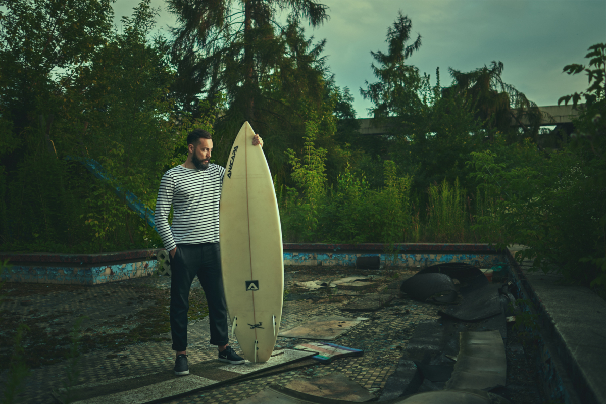 Picture of Son of a Beach blogger standing in abandoned swimming pool with a surfboard watching the sunset