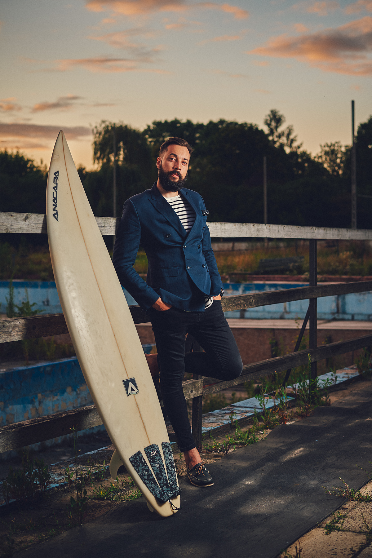 Picture of Son of a Beach blogger wearing double-brested jacket with surfboard next to him and sunset behind him