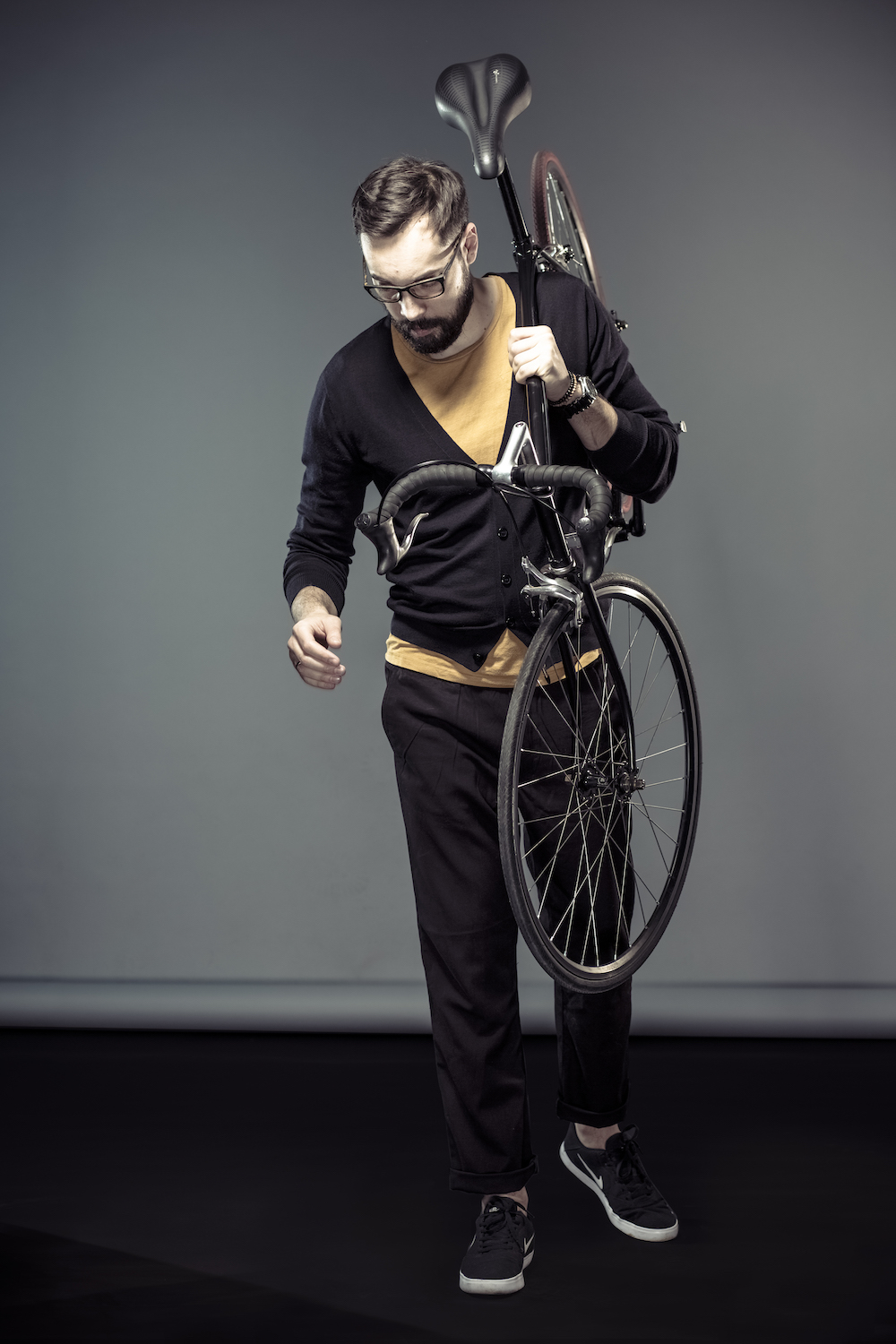 man wearing stylish cardigan and carrying a city bike