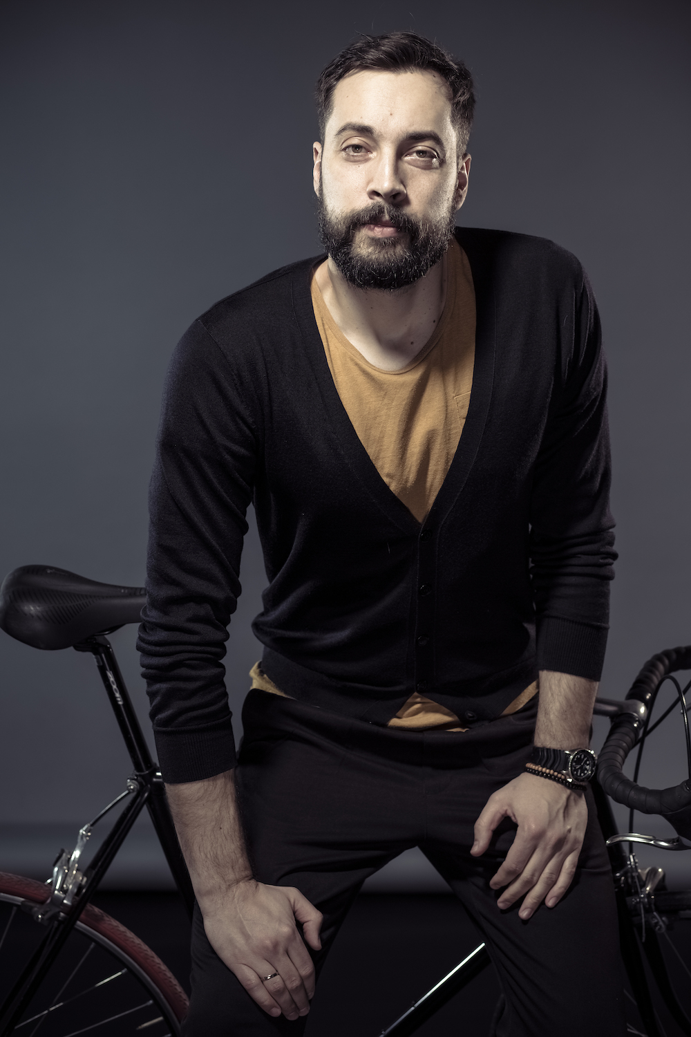 man wearing a black cardigan sitting on a bike