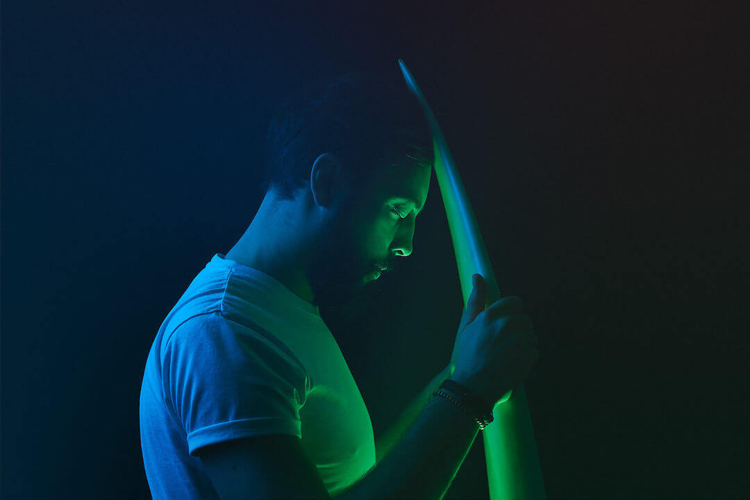 Bearded man with a surfboard in a neon photo session