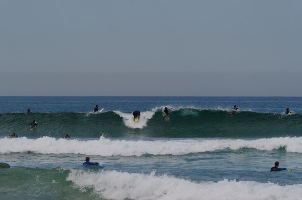 surfer łapiący falę na plaży w Guincho