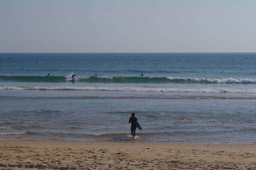 surfer wchodzący do wody na plaży w Carcavelos