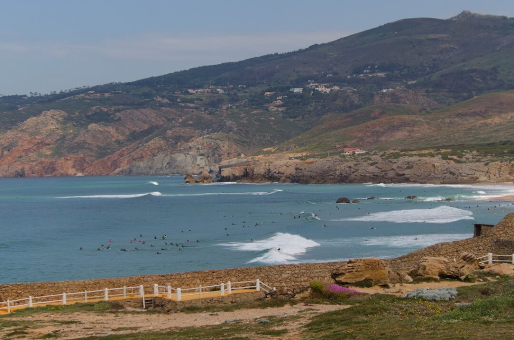 surfers sitting on a lineup waiting for waves at Guincho beach, Portugal